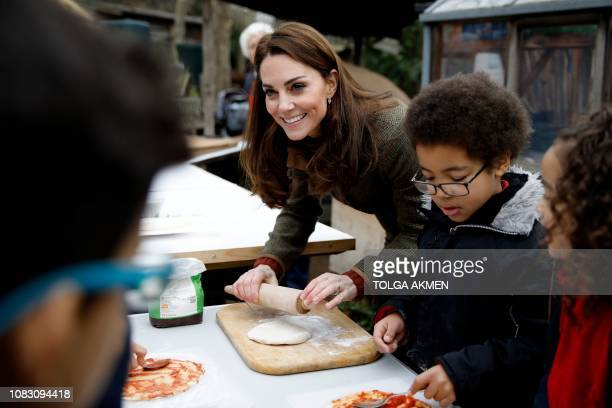 Britain's Catherine Duchess of Cambridge helps to make pizza with children as she visits the Islington community garden in north London on January 15...