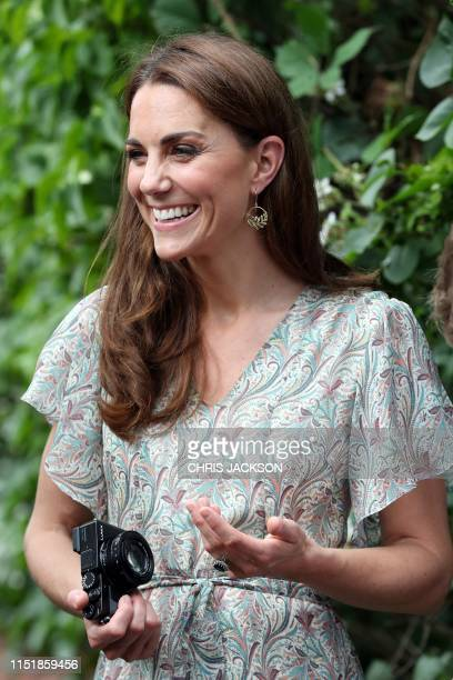 Britain's Catherine Duchess of Cambridge holds a camera as she takes part in a a photography workshop with the charity 'Action for Children' in...