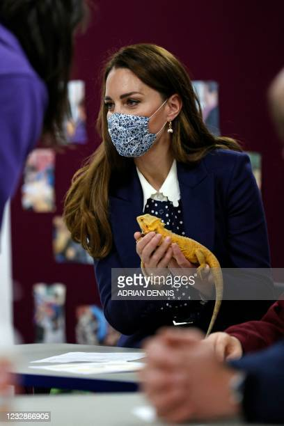 Britain's Catherine, Duchess of Cambridge, holds a chameleon as she joins a group of local school children from Loxdale Primary School during a visit...