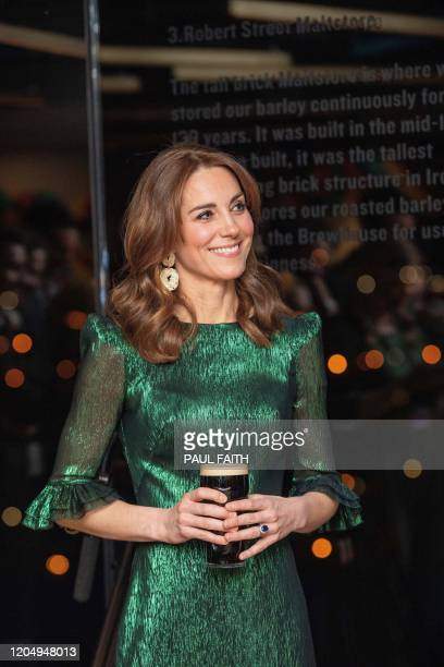 Britain's Catherine Duchess of Cambridge holds a pint of Guinness as they attend a special reception at the Guinness Storehouses Gravity Bar in...
