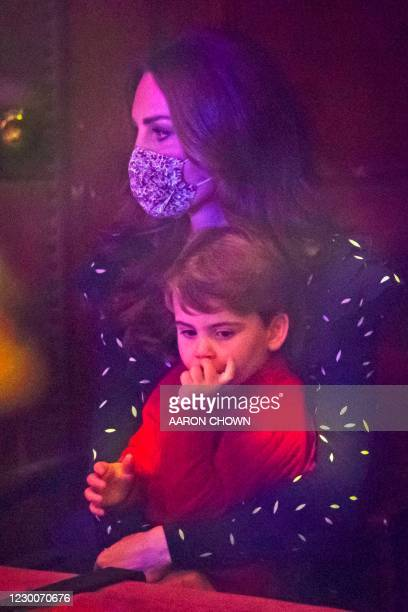 Britain's Catherine, Duchess of Cambridge holds Britain's Prince Louis of Cambridge during a special pantomime performance of The National Lotterys...