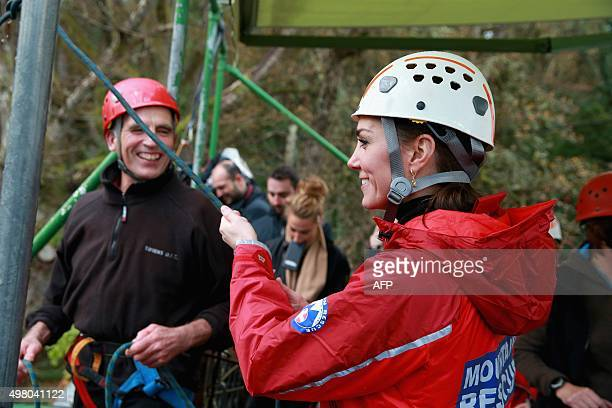 Britain's Catherine Duchess of Cambridge holds Prince William Duke of Cambridge's support rope as he abseils during a visit to the Towers Residential...