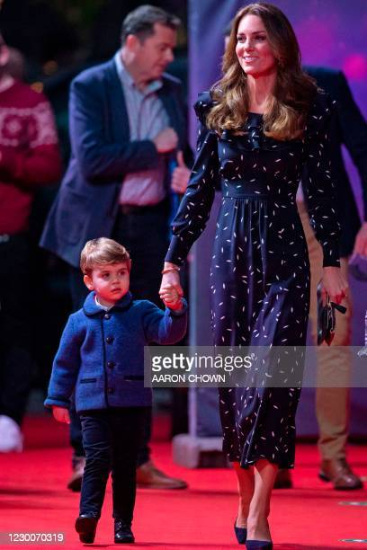 Britain's Catherine, Duchess of Cambridge, holds the hand of her son, Britain's Prince Louis of Cambridge as they attend a special pantomime...