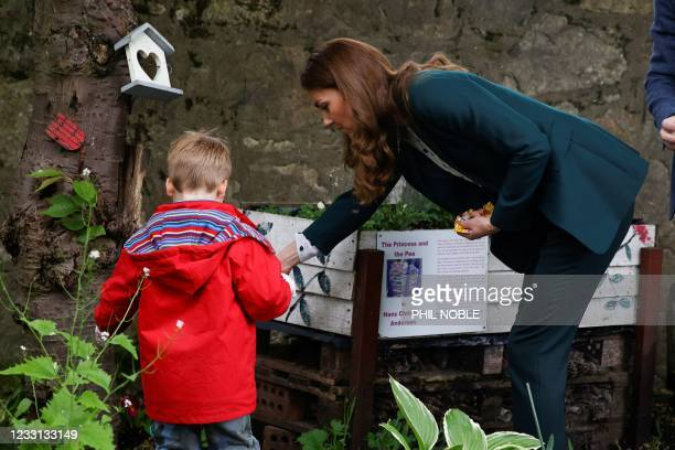 Britain's Catherine, Duchess of Cambridge interacts with a child from Edzell Nursery as she visits Starbank Park to hear about the work of Fields in...