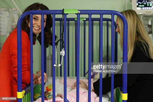 Britain's Catherine Duchess of Cambridge interacts with sixmonth old patient Sienna McGuire during her visit to officially open the Mittal Children's...