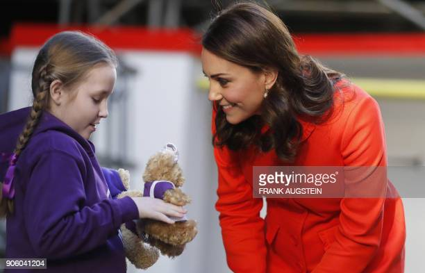 Britain's Catherine Duchess of Cambridge is given two teddy bears by patient Eva during her visit to officially open the Mittal Children's Medical...
