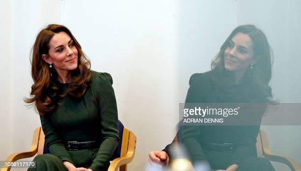 TOPSHOT Britain's Catherine Duchess of Cambridge is reflected in a glass door as she looks towards Family Action CEO David Holmes as he speaks with...