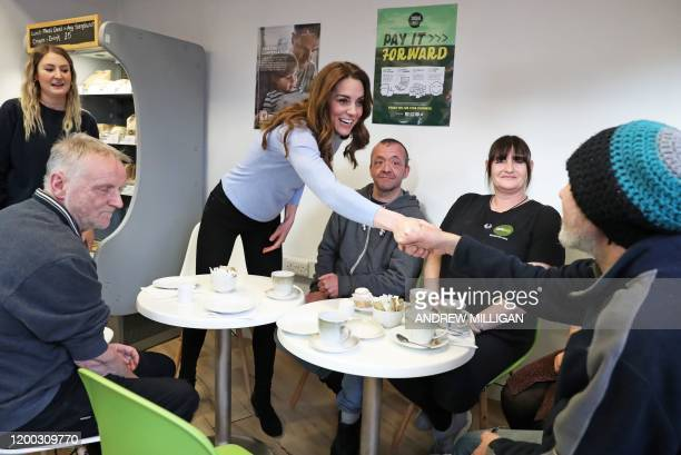 Britain's Catherine, Duchess of Cambridge, known as the Countess of Strathearn while in Scotland, speaks to clients during her visit to the Social...