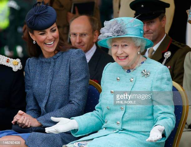 Britain's Catherine, Duchess of Cambridge laughs as Britain's Queen Elizabeth II gestures as they watch part of a children's sports event on their...