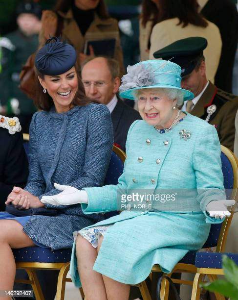 Britain's Catherine Duchess of Cambridge laughs as Britain's Queen Elizabeth II gestures as they watch part of a children's sports event on their...