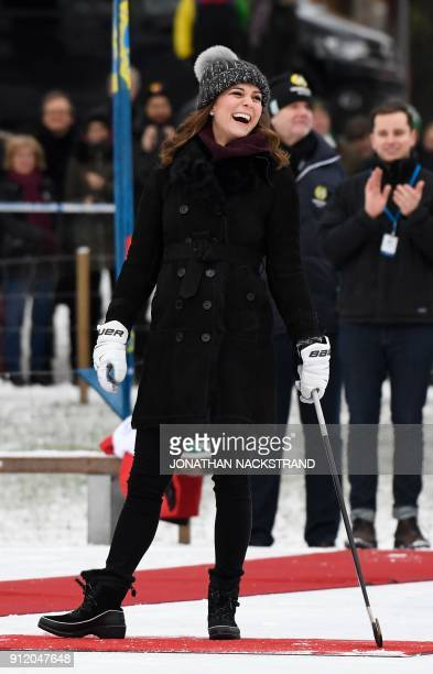 TOPSHOT Britain's Catherine Duchess of Cambridge laughs as she trys out the game of bandy during a meeting with a group of local bandy players on the...