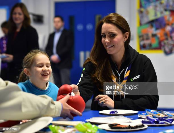 Britain's Catherine Duchess of Cambridge learns about disability by wearing a boxing glove to handle a fork as she meets with children at the newly...
