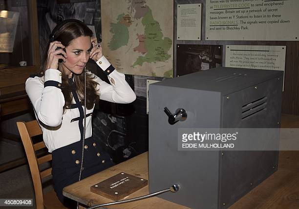 Britain's Catherine Duchess of Cambridge listens to an intercepted coded message as she views the restored WWII codebreaking huts during a visit to...