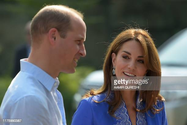 Britain's Catherine Duchess of Cambridge looks at her husband Prince William Duke of Cambridge as they meet with school officials during their visit...