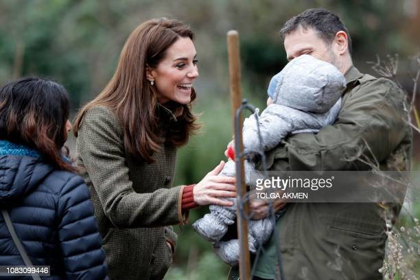 Britain's Catherine Duchess of Cambridge meets a young baby as she visits the Islington community garden in north London on January 15 2019