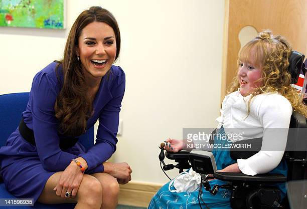 Britain's Catherine Duchess of Cambridge meets Bethany Woods in a music class during a visit to The Treehouse in Ipswich eastern England on March 19...