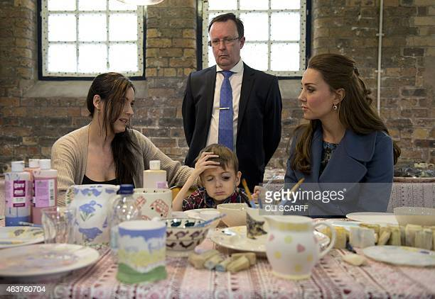 Britain's Catherine Duchess of Cambridge meets Sarah O'Sullivan and her disabled 4yearold son Daniel as they decorate crockery during a visit at the...