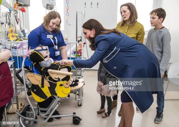 Britain's Catherine Duchess of Cambridge meets ten month old Amara Kedwell Parsons who was born prematurely and is a patient on the children's Snow...