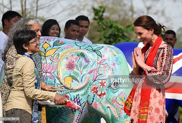 Britain's Catherine Duchess of Cambridge meets wildlife officials next to elephant statues painted by children at Kaziranga Discovery Park in Panbari...