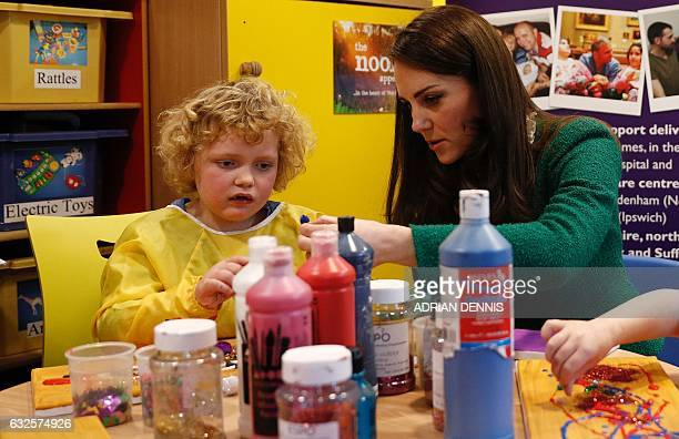 Britain's Catherine Duchess of Cambridge participates in a craft session with Isabella Benton in the Art Therapy room during her to visit East...
