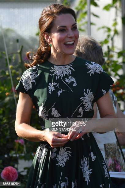 Britain's Catherine Duchess of Cambridge reacts after trying a tomato at the 'BBC Radio 2 Chris Evans Taste Garden' during her visit to the Chelsea...