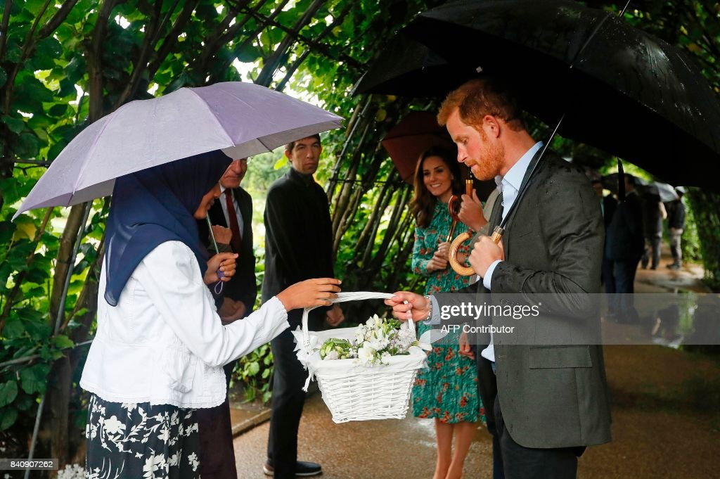Britain's Catherine, Duchess of Cambridge (C) reacts as Britain's Prince Harry (R), is presented with a basket of flowers during an event at the memorial gardens in Kensington Palace, west London on August 30, 2017. Princes William and Harry prepared to pay tribute to their late mother Princess Diana on Wednesday for the 20th anniversary of her death as wellwishers left candles and flowers outside the gates of her former London residence. The Princes visited the Sunken Garden in the grounds of Kensington Palace, which this year has been transformed into a White Garden, dedicated to their late mother, Britain's Diana, Princess of Wales. / AFP PHOTO / POOL / Kirsty Wigglesworth
