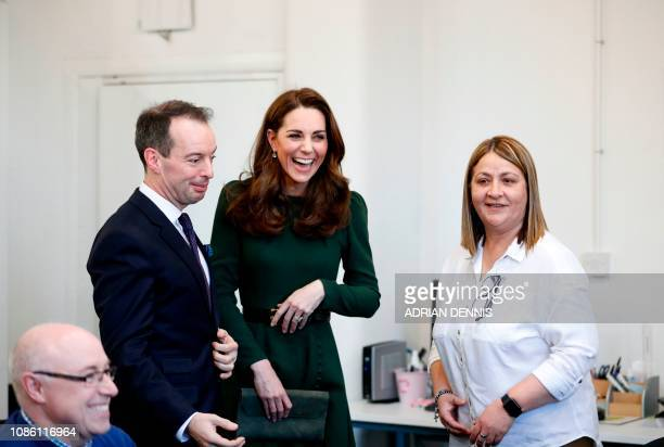 Britain's Catherine Duchess of Cambridge reacts as she is introduced to staff members during a visit Family Action in Lewisham south London on...