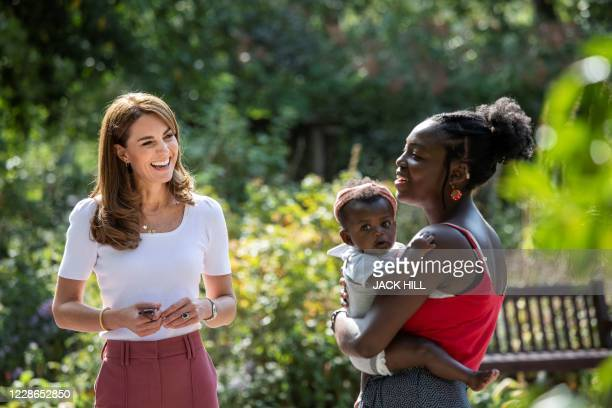 Britain's Catherine, Duchess of Cambridge, reacts as she meets with Morgan Alex Cassius and her six-month-old daughter, Makena Grace, in Battersea...