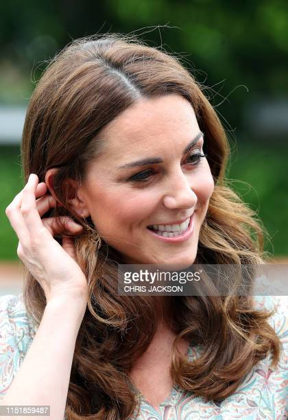 Britain's Catherine Duchess of Cambridge reacts as she takes part in a a photography workshop with the charity 'Action for Children' in Kingston...