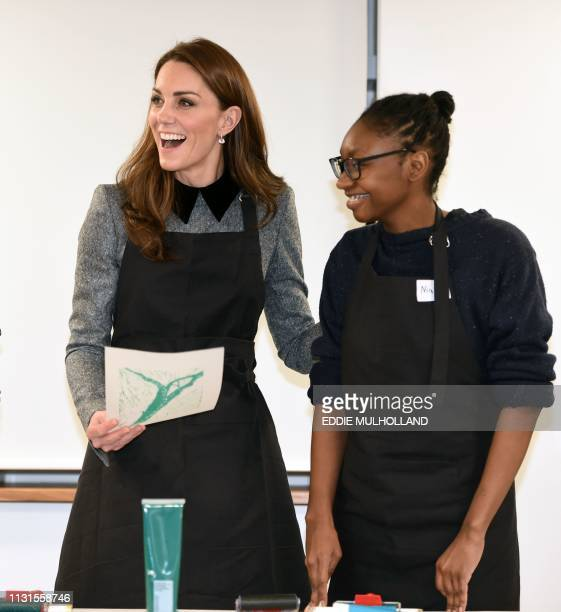 Britain's Catherine Duchess of Cambridge reacts as she takes part in an activity during her visit to the Foundling Museum where young people are...