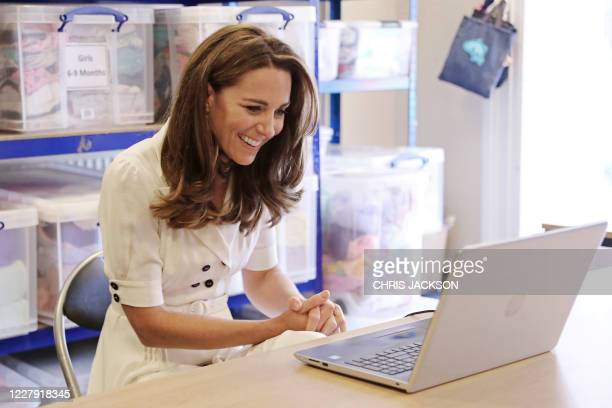 Britain's Catherine, Duchess of Cambridge reacts as she uses a computer to take part in a video conference call with other baby banks during her...