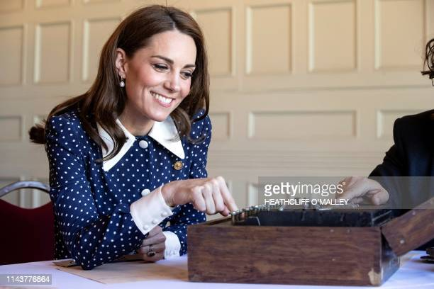 Britain's Catherine Duchess of Cambridge reacts as she uses an Enigma cipher code machine during her visit to Bletchley Park in Bletchley north west...