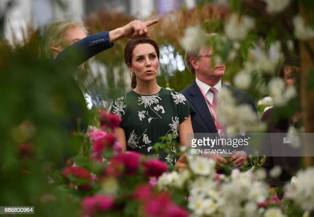 Britain's Catherine Duchess of Cambridge reacts as she views a display of David Austin roses at the Chelsea Flower Show in London on May 22 2017 The...