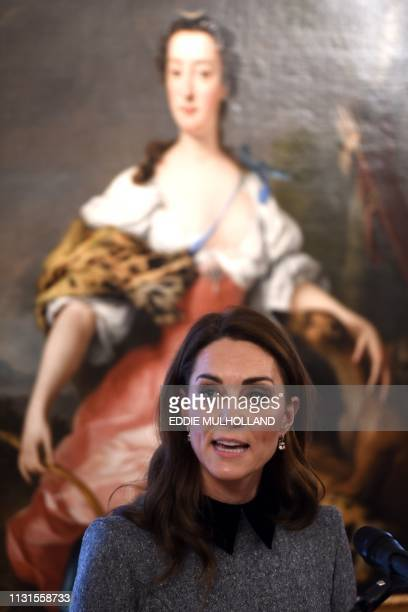 Britain's Catherine Duchess of Cambridge reacts during her visit to the Foundling Museum where young people are taught to use art in order to make a...