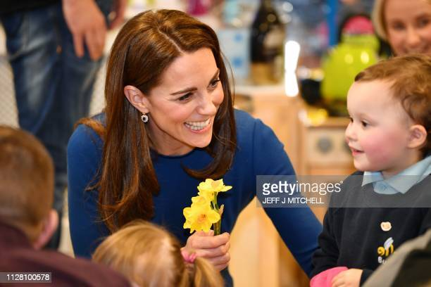Britain's Catherine, Duchess of Cambridge receives a bunch of daffodils from a small child during a visit to St Josephs Sure Start Facility in...