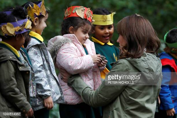 Britain's Catherine Duchess of Cambridge receives a hug from fouryearold Amwaar as she says goodbye to school children after visiting to Sayers Croft...