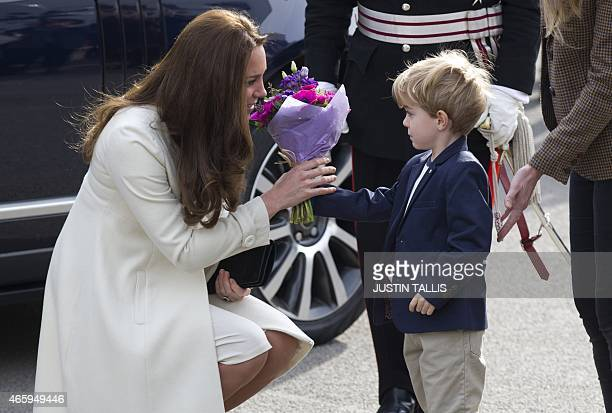 Britain's Catherine Duchess of Cambridge receives flowers from actor Zac Barker on the set of British television series Downton Abbey at Ealing...