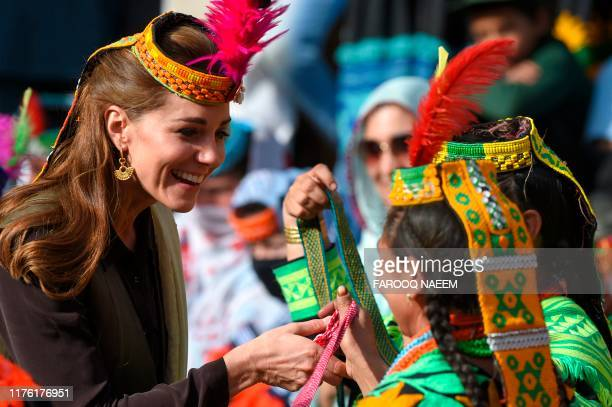 Britain's Catherine , Duchess of Cambridge, receives gifts from a member of the Kalash tribe during her visit to theBumburate Valley in Pakistan...