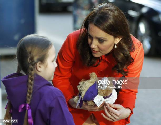 Britain's Catherine Duchess of Cambridge receives two teddy bears from patient Eva during her visit to officially open the Mittal Children's Medical...