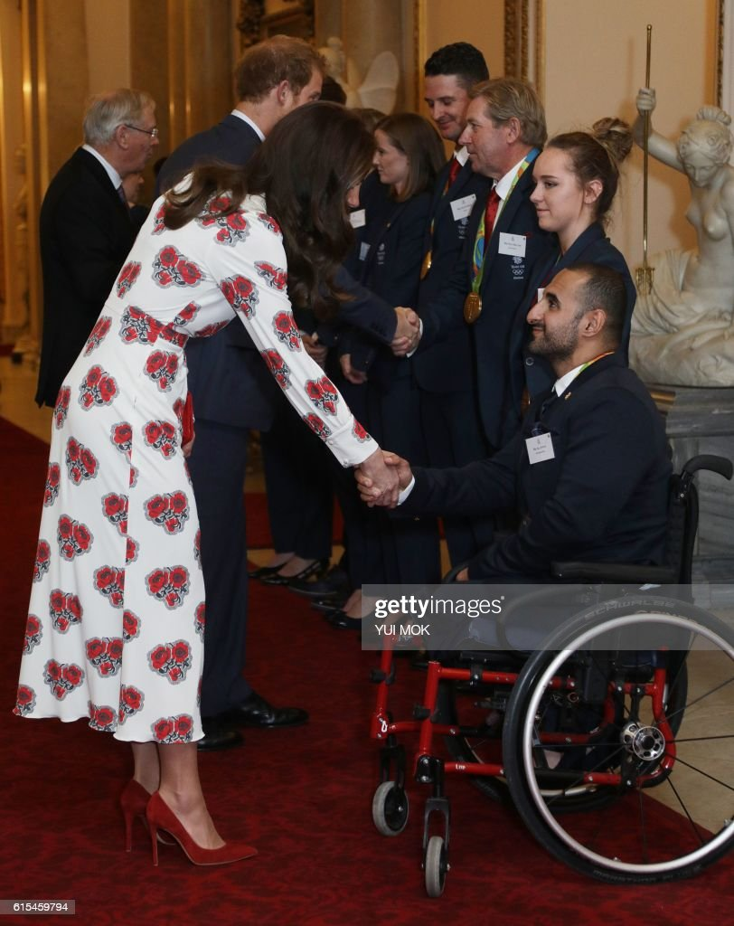 Britain's Catherine, Duchess of Cambridge (L) shakes hands with paralympic athlete Ali Jawad, as she meet athletes during a reception for Team GB's Olympic and Paralympic athletes, hosted by Britain's Queen Elizabeth II, at Buckingham Palace in central London on October 18, 2016. Britain's stars of this year's Olympic and Paralympic Games in Rio attended an 'amazing' reception at Buckingham Palace -- the official London home of Queen Elizabeth II -- on Tuesday. / AFP PHOTO / POOL / Yui Mok