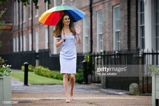 Britain's Catherine, Duchess of Cambridge, shelters from the rain under an umbrella as she arrives at Kensington Palace to meet with a group of...