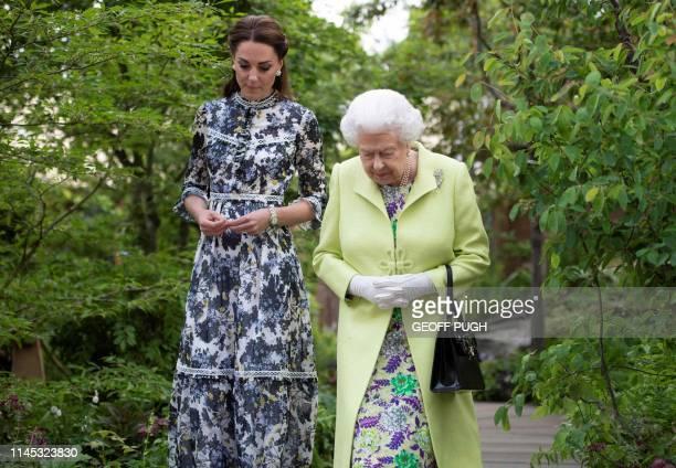 TOPSHOT Britain's Catherine Duchess of Cambridge shows Britain's Queen Elizabeth II and Britain's Prince William Duke of Cambridge around the 'Back...
