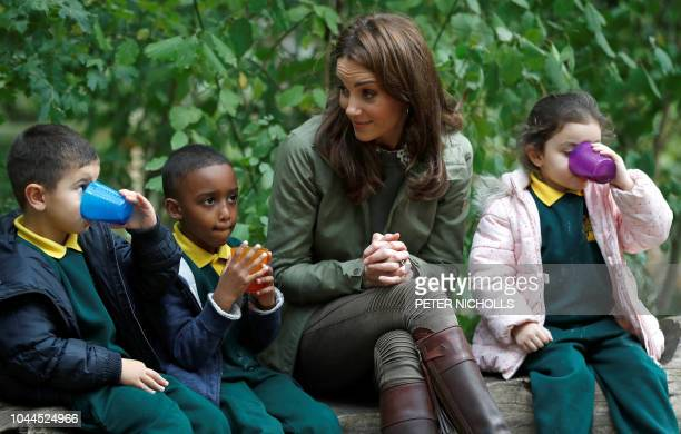 TOPSHOT Britain's Catherine Duchess of Cambridge sits on a log with school children during her visit to Sayers Croft Forest School and Wildlife...