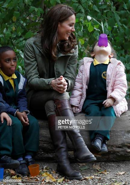 Britain's Catherine Duchess of Cambridge sits on a log with school children during her visit to Sayers Croft Forest School and Wildlife Garden in...