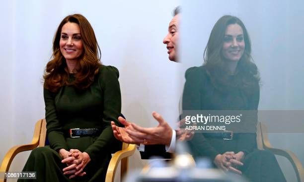 Britain's Catherine Duchess of Cambridge sits with Family Action CEO David Holmes as he speaks with people supported by the charity during a visit to...