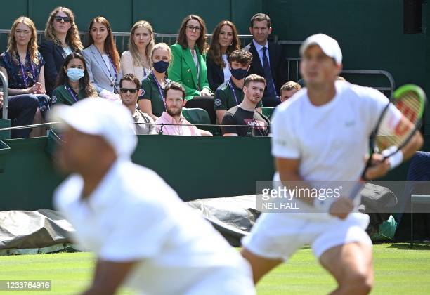 Britain's Catherine, Duchess of Cambridge sits with former player Tim Henman to watch Britain's Jamie Murray and Brazil's Bruno Soares play against...