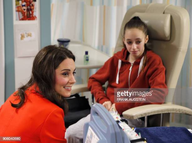Britain's Catherine Duchess of Cambridge sits with patient Gabriella Cook during her visit to officially open the Mittal Children's Medical Centre...