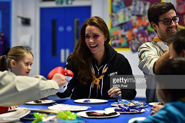 Britain's Catherine Duchess of Cambridge sitting beside Scout Leader Carlos LopezPlandolit learns about disability by wearing a boxing glove to...