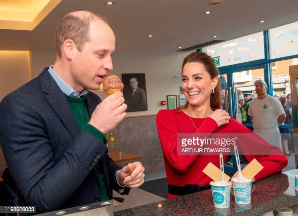 Britain's Catherine Duchess of Cambridge smiles as her husband Britain's Prince William Duke of Cambridge tastes an ice cream at the counter during...