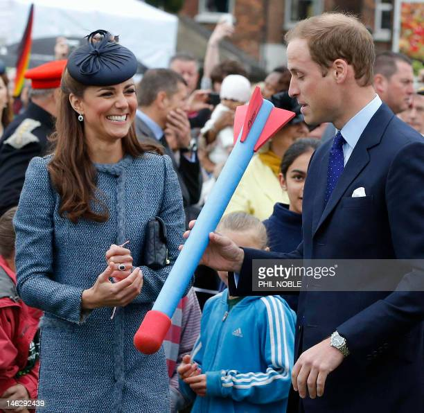 Britain's Catherine Duchess of Cambridge smiles as her husband Prince William holds a foam javelin as they join in with a children's sports event...